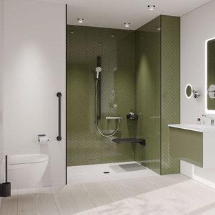 Inredning av ett modernt mycket stort badrum med dusch, med luckor med infälld panel, gröna skåp, en kantlös dusch, en vägghängd toalettstol, grön kakel, mosaik, vita väggar, ett integrerad handfat, bänkskiva i glas, grått golv och med dusch som är öppen