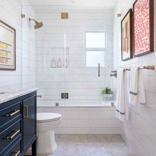 Klassisches Badezimmer mit Schrankfronten mit vertiefter Füllung, blauen Schränken, Unterbauwanne, Duschbadewanne, weißer Wandfarbe, Unterbauwaschbecken, grauem Boden, Falttür-Duschabtrennung, weißer Waschtischplatte, Nische, Einzelwaschbecken und freistehendem Waschtisch in San Francisco