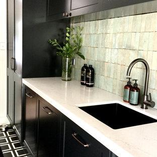 Inredning av en lantlig mellanstor vita linjär vitt tvättstuga enbart för tvätt, med en undermonterad diskho, skåp i shakerstil, svarta skåp, bänkskiva i kvarts, grönt stänkskydd, stänkskydd i terrakottakakel, vita väggar, betonggolv, en tvättmaskin och torktumlare bredvid varandra och svart golv