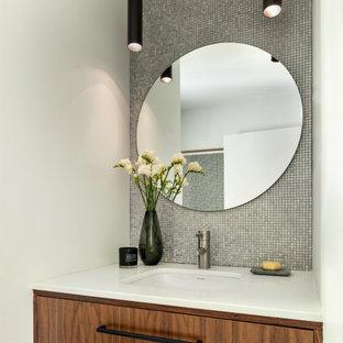 Esempio di una stanza da bagno minimal di medie dimensioni con consolle stile comò, ante marroni, WC monopezzo, piastrelle in metallo, pareti bianche, pavimento in gres porcellanato, lavabo sottopiano, pavimento grigio, top bianco, un lavabo e mobile bagno sospeso