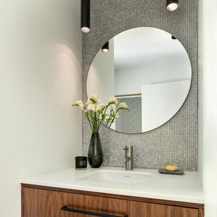 Photo of a mid-sized contemporary bathroom in New York with furniture-like cabinets, brown cabinets, a one-piece toilet, metal tile, white walls, porcelain floors, an undermount sink, grey floor, white benchtops, a single vanity and a floating vanity.