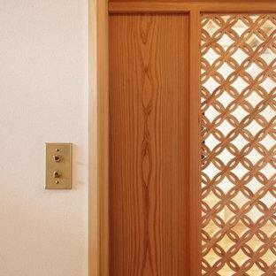 Idee per un piccolo corridoio etnico con pareti bianche, pavimento in legno massello medio, una porta scorrevole, una porta in legno bruno, pavimento arancione e soffitto in legno