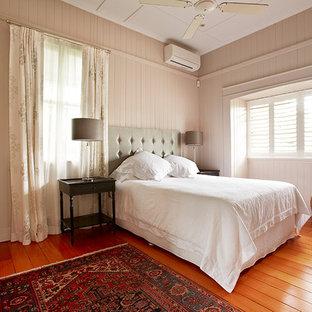 Esempio di una camera matrimoniale eclettica con pavimento in legno massello medio