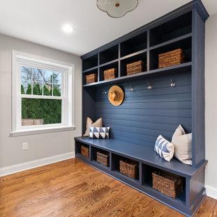 Mittelgroßer Landhausstil Eingang mit Stauraum, grauer Wandfarbe, braunem Holzboden und Holzdielenwänden in Philadelphia