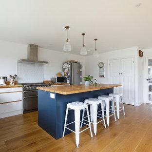 サセックスの広いコンテンポラリースタイルのおしゃれなキッチン (ダブルシンク、フラットパネル扉のキャビネット、白いキャビネット、木材カウンター、白いキッチンパネル、セラミックタイルのキッチンパネル、シルバーの調理設備、無垢フローリング、茶色い床、茶色いキッチンカウンター) の写真