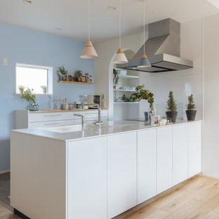 他の地域の中くらいの北欧スタイルのおしゃれなキッチン (フラットパネル扉のキャビネット、白いキャビネット、白いキッチンパネル、淡色無垢フローリング、ベージュの床、白いキッチンカウンター、クロスの天井) の写真