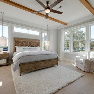 Immagine di una grande camera matrimoniale stile marino con pareti grigie, parquet chiaro, pavimento grigio e travi a vista
