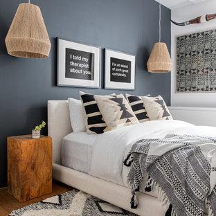 Kleines Modernes Gästezimmer mit schwarzer Wandfarbe und braunem Holzboden in New York