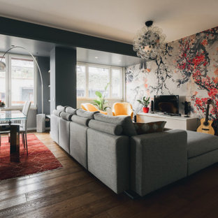 Immagine di un grande soggiorno minimal aperto con libreria, pareti grigie, parquet chiaro, parete attrezzata, pavimento marrone e soffitto ribassato