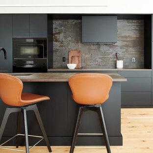 Inspiration för ett mellanstort funkis flerfärgad linjärt flerfärgat kök och matrum, med en undermonterad diskho, släta luckor, svarta skåp, bänkskiva i kvartsit, flerfärgad stänkskydd, svarta vitvaror, bambugolv, en köksö och brunt golv