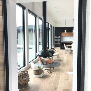 Idee per un grande soggiorno minimalista aperto con pareti bianche, parquet chiaro, camino sospeso, TV a parete e pavimento grigio
