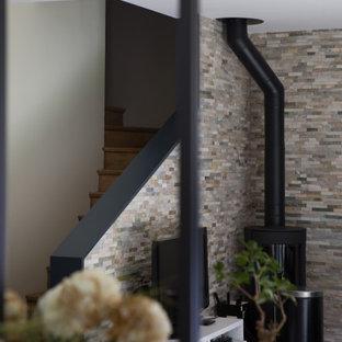 Mittelgroßes, Offenes Modernes Wohnzimmer mit beiger Wandfarbe, hellem Holzboden, Kaminofen, Kaminumrandung aus Metall, beigem Boden und Ziegelwänden in Paris