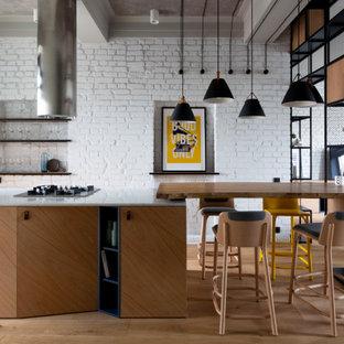Идея дизайна: кухня-гостиная в стиле лофт с плоскими фасадами, фасадами цвета дерева среднего тона и островом
