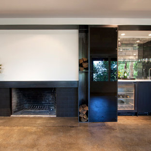 This is an example of a contemporary single-wall wet bar in Portland with concrete flooring, flat-panel cabinets, black cabinets, marble worktops and mirror splashback.