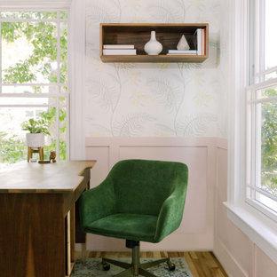 Klassisches Arbeitszimmer mit rosa Wandfarbe, hellem Holzboden, braunem Boden und vertäfelten Wänden in Austin