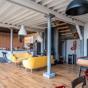 Foto de salón abierto, industrial, grande, con paredes negras, suelo de madera clara, estufa de leña, marco de chimenea de metal y suelo marrón