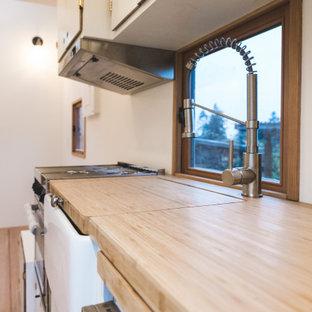 バンクーバーの小さいコンテンポラリースタイルのおしゃれなI型キッチン (エプロンフロントシンク、フラットパネル扉のキャビネット、白いキャビネット、木材カウンター、白いキッチンパネル、木材のキッチンパネル、シルバーの調理設備、無垢フローリング、アイランドなし、赤い床、茶色いキッチンカウンター、板張り天井) の写真