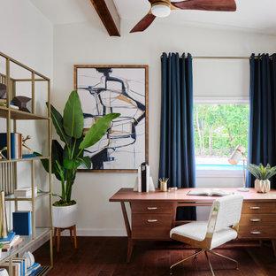 Mittelgroßes Retro Arbeitszimmer mit Arbeitsplatz, weißer Wandfarbe, braunem Holzboden, freistehendem Schreibtisch, braunem Boden und freigelegten Dachbalken in Austin