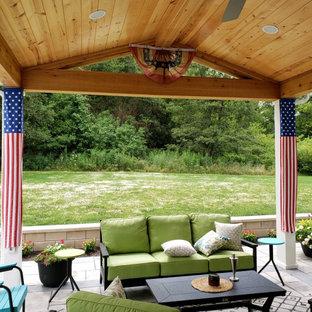 Foto di un ampio patio o portico eclettico dietro casa con un focolare, un tetto a sbalzo e cemento stampato