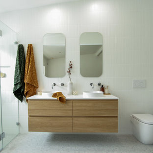 Photo of a mid-sized contemporary 3/4 bathroom in Sydney with medium wood cabinets, a one-piece toilet, white tile, white walls, a vessel sink, grey floor, a hinged shower door, white benchtops, a niche, a double vanity and a floating vanity.