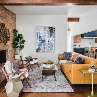 Mittelgroßes, Offenes Retro Wohnzimmer mit weißer Wandfarbe, braunem Holzboden, Kamin, Kaminumrandung aus gestapelten Steinen, braunem Boden und freigelegten Dachbalken in Austin