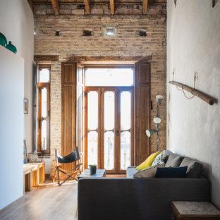 Modelo de salón tipo loft y ladrillo, industrial, pequeño, ladrillo, con paredes blancas, suelo de madera oscura y ladrillo