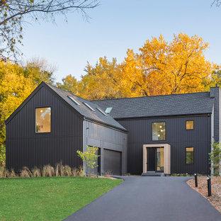 Пример оригинального дизайна: большой, двухэтажный, деревянный, черный частный загородный дом в скандинавском стиле с двускатной крышей, крышей из гибкой черепицы, черной крышей и отделкой доской с нащельником