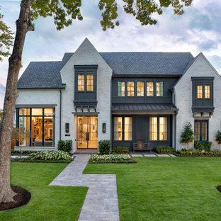 ヒューストンの巨大なトランジショナルスタイルのおしゃれな家の外観 (混合材サイディング、マルチカラーの外壁、縦張り) の写真