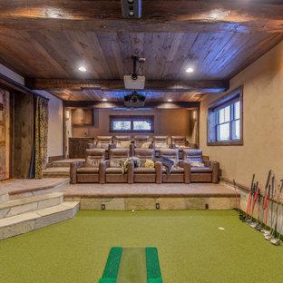 Réalisation d'un grand sous-sol chalet semi-enterré avec salle de cinéma, un mur beige, aucune cheminée, un sol vert et un plafond en lambris de bois.
