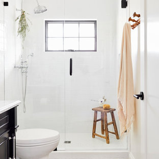 Inspiration for a medium sized mediterranean shower room bathroom in Los Angeles with freestanding cabinets, black cabinets, an alcove shower, a two-piece toilet, white tiles, ceramic tiles, white walls, cement flooring, a submerged sink, marble worktops, white floors, a hinged door and white worktops.