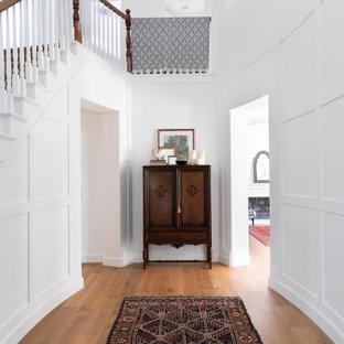 Idee per un grande ingresso classico con pareti bianche, pavimento in legno massello medio, pavimento marrone e pannellatura