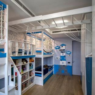 Inspiration för ett mellanstort funkis pojkrum kombinerat med sovrum och för 4-10-åringar, med blå väggar, ljust trägolv och beiget golv