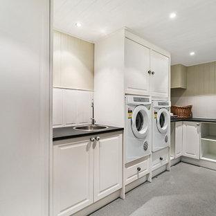 Bild på en mycket stor vintage svarta l-formad svart tvättstuga enbart för tvätt, med en nedsänkt diskho, skåp i shakerstil, vita skåp, laminatbänkskiva, vitt stänkskydd, stänkskydd i keramik, beige väggar, vinylgolv, en tvättmaskin och torktumlare bredvid varandra och grått golv
