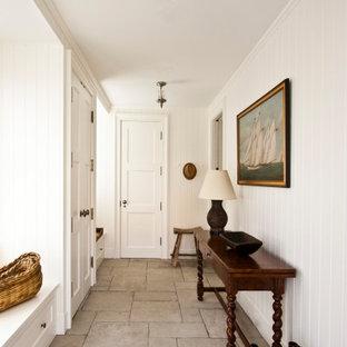 Пример оригинального дизайна: маленький тамбур в классическом стиле с белыми стенами, полом из известняка, одностворчатой входной дверью, белой входной дверью и бежевым полом