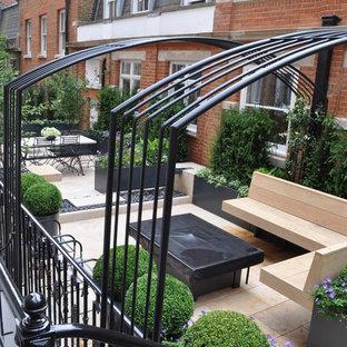 Idee per un piccolo giardino formale minimal sul tetto con pavimentazioni in pietra naturale e un focolare