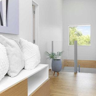 Пример оригинального дизайна: коридор среднего размера в современном стиле с белыми стенами, полом из ламината и коричневым полом