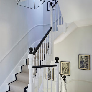 Photo of a medium sized traditional painted wood curved wood railing staircase in London with painted wood risers.