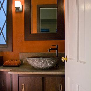 Exemple d'un petit WC et toilettes asiatique avec un placard à porte plane, des portes de placard en bois sombre, un mur rouge et une vasque.