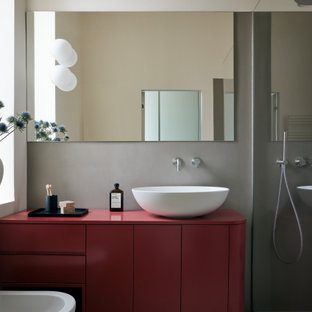 Contemporary 3/4 bathroom in Milan with red cabinets, cement tiles, a vessel sink, red benchtops, a single vanity and a freestanding vanity.