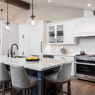 На фото: большая кухня в стиле неоклассика (современная классика) с обеденным столом, монолитной раковиной, фасадами в стиле шейкер, белыми фасадами, столешницей из кварцевого агломерата, белым фартуком, фартуком из кирпича, техникой под мебельный фасад, паркетным полом среднего тона, островом, разноцветным полом, белой столешницей и сводчатым потолком с