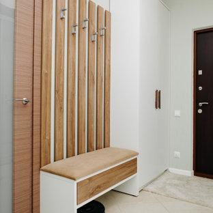 Modern inredning av en liten hall, med gröna väggar, klinkergolv i keramik, en enkeldörr, metalldörr och beiget golv