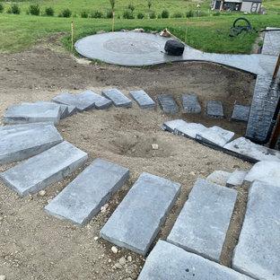 Immagine di una piccola scala curva chic con pedata in cemento, alzata in cemento, parapetto in materiali misti e pareti in mattoni