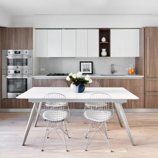 This is an example of a mid-sized contemporary eat-in kitchen in New York with a single-bowl sink, medium wood cabinets, granite benchtops, white splashback, granite splashback, stainless steel appliances, medium hardwood floors, beige floor and white benchtop.