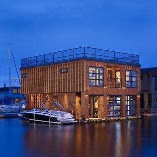 Ispirazione per la facciata di una casa unifamiliare piccola marrone industriale a due piani con rivestimento in legno, tetto piano e copertura verde