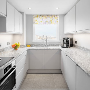 This is an example of a small contemporary u-shaped enclosed kitchen in Sussex with a submerged sink, flat-panel cabinets, grey cabinets, quartz worktops, integrated appliances, porcelain flooring, no island, grey floors and multicoloured worktops.