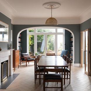 ロンドンの広いコンテンポラリースタイルのおしゃれな独立型ダイニング (青い壁、淡色無垢フローリング、吊り下げ式暖炉、石材の暖炉まわり、ベージュの床、格子天井) の写真