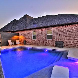 Modelo de piscina moderna, de tamaño medio, rectangular, en patio trasero, con adoquines de piedra natural
