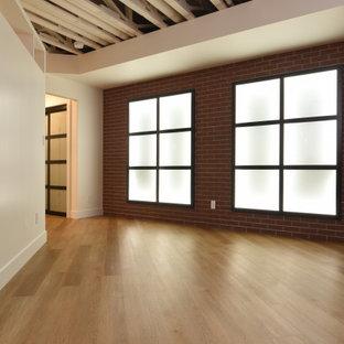Exemple d'un grand sous-sol tendance enterré avec salle de jeu, un mur blanc, un sol en vinyl, une cheminée standard, un manteau de cheminée en bois et un sol beige.