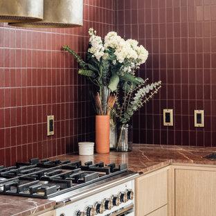Mittelgroße Mid-Century Wohnküche in L-Form mit integriertem Waschbecken, flächenbündigen Schrankfronten, hellen Holzschränken, Marmor-Arbeitsplatte, Küchenrückwand in Rot, Rückwand aus Glasfliesen, weißen Elektrogeräten, Terrazzo-Boden, Halbinsel, grauem Boden, roter Arbeitsplatte und freigelegten Dachbalken in Salt Lake City
