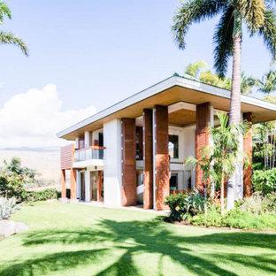 Inspiration för ett mycket stort tropiskt vitt hus, med två våningar, stuckatur och tak med takplattor